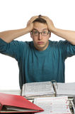 Too much paperwork. One man sitting in front of too much paperwork holding his head Royalty Free Stock Images