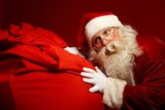 Too much presents. Santa Claus pushing a big sack Stock Photo