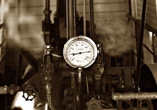 Too much pressure gauge blows. Sepia image of machinery under pressure gauge lets out steam royalty free stock photos