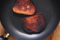 Too much roasted toast on a frying pan Stock Photography
