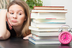 Too much study. A young woman glances sideways at the large pile of books for exam study time.  Time ticks on reminding her of the limited time to finish the Stock Image