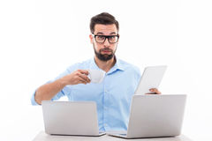 Too much technology. Young man at desk with laptops Royalty Free Stock Photography