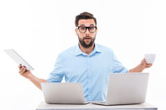 Too much technology. Young man at desk with laptops Stock Photos
