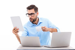 Too much technology. Young man at desk with laptops Stock Images