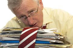 Too much work. An exhausted businessman has had too much of his paperwork stock photo