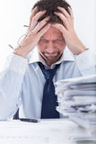 Too much work. Portrait of exhausted businessman sitting at office desk full with papers Stock Image