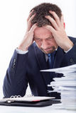 Too much work. Portrait of exhausted businessman sitting at office desk full with papers Stock Photos