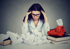 Too much work stressed woman sitting at her disorganized desk with books and many paper balls. On gray office wall background Stock Photos
