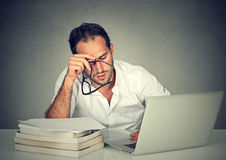 Too much work tired sleepy man sitting at desk Stock Image