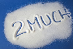 TOO MUCH written with sugar. Sugar on a blue background with warning message 2 MUCH written on it. Health concept. Diabetes hazard Stock Photo