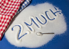 TOO MUCH written with sugar. Sugar on a blue background with warning message 2 MUCH written on it. Health concept. Diabetes hazard Royalty Free Stock Image