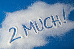 TOO MUCH written with sugar. Sugar on a blue background with warning message 2 MUCH written on it. Health concept. Diabetes hazard Stock Image