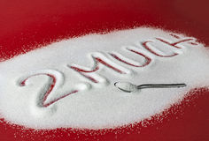 TOO MUCH written with sugar. Sugar on a red background with warning message 2 MUCH written on it. Health concept. Diabetes hazard Royalty Free Stock Photography