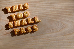 This too shall pass. Edible letters. This too shall pass. Text from the salty crackers as printed English letters that lie on a wooden chopping board. Message Royalty Free Stock Images