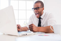 Too stressful work. Furious young African man in shirt and tie shouting while looking at laptop while sitting at his working place Stock Photos