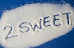 TOO SWEET written with  sugar. Sugar on a blue background with warning message 2 SWEET written on it. Health concept. Diabetes hazard Royalty Free Stock Photo