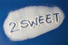 TOO SWEET written with  sugar. Sugar on a blue background with warning message 2 SWEET written on it. Health concept. Diabetes hazard Stock Photos