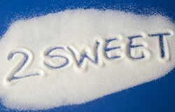 TOO SWEET written with  sugar. Sugar on a blue background with warning message 2 SWEET written on it. Health concept. Diabetes hazard Royalty Free Stock Image