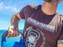 Too Tight Kettlebell Grip. Taco Fleur from Cavemantraining demonstrates the incorrect tight grip on a kettlebell. Background shows the Mediterranean sea on the Royalty Free Stock Image