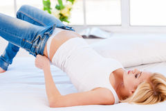 Too tight. Young blond hair woman lying on the bed and pulling on tight jeans royalty free stock photo