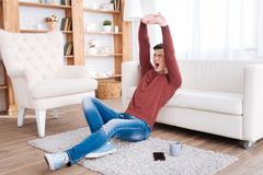 Exhausted pretty man wanting relax. Too tired. Appealing tired man stretching while sitting on floor stock photo