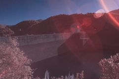 Surreal water dam in infrared colors. Took with IR 650nm,waterdam next to small mountains, surrounded by lots of trees, dreamy colors Royalty Free Stock Photography
