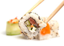 Took a maki sushi. Took a sushi roll by the chopsticks Royalty Free Stock Images