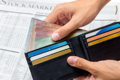 Took the money out of pocket over stock market newspaper Royalty Free Stock Image