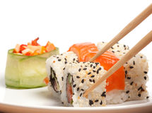 Took a sushi. Sushi roll in the chopsticks Royalty Free Stock Images