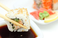 Took a sushi roll by the chopsticks Stock Photo