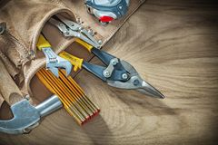 Tool belt with construction tooling on wooden board Stock Image