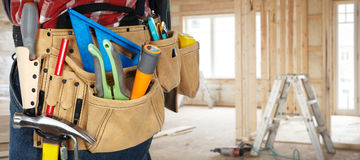 Tool belt with construction tools. Builder handyman with construction tools on renovation background Stock Photo