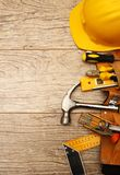Tool belt and tools. Tool belt with hand tools and yellow helmet royalty free stock photo