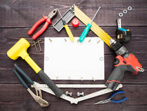 The tool building on the wooden background around the white sheet of paper royalty free stock photos