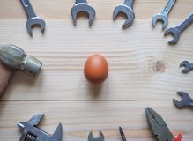 Tool and egg on wooden background. The concept of complex problems, the challenge can be solved. Tool and egg on wooden background. The concept of complex Royalty Free Stock Photos