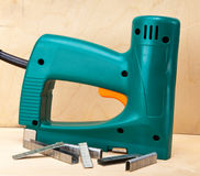 The tool - an electrical stapler for repair work in the house and on furniture, and brackets.Close up in a sunny day Stock Photos