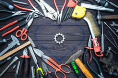 Tool and heart on dark wooden background. Love for your work, Father`s Day stock photo