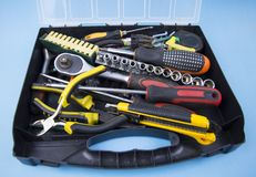 Tool kit: wrenches, screwdrivers, pliers, stacked chaotically in a plastic case on a blue background royalty free stock photos