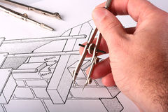 Tool over the drawing. The man's hand holds the measuring drawing tool over the drawing Stock Photo