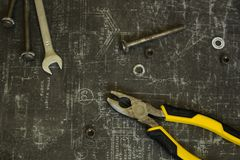 Tool set of pliers, wrenches, bolts and nuts on abstract grey surface royalty free stock photos