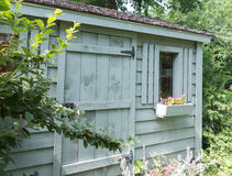 Tool shed. Wooden garden shed surrounded by foliage Stock Photo
