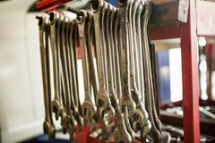 Close-up of spanner tool of various sizes arranged in line with red car tool box. Tool to tighten or loosen the head of a bolt, nut, or screw/There is one Royalty Free Stock Photo