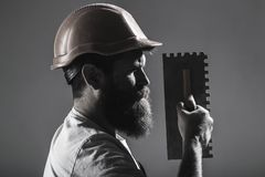 Tool, trowel, handyman, man builder. Mason tools, builder. Bearded man worker, beard, building helmet, hard hat. Builders in hard hat, helmet Mason plastering stock photo