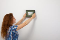 Tool and work. A young woman hangs a picture on Stock Photo