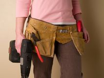 Toolbelt. Girl wearing a toolbelt and holding a drill Stock Photography