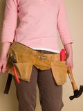 Toolbelt. Girl holding a hammer and wearing a toolbelt Royalty Free Stock Image