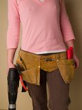 Toolbelt. Girl holding a drill and wearing a toolbelt Royalty Free Stock Photos