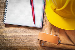 Toolbelt building helmet copybook pen on wooden board Royalty Free Stock Images