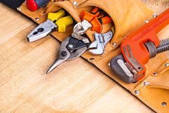 Toolbelt with tools on wooden board Royalty Free Stock Photography