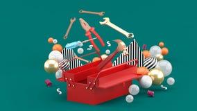 Toolbox между красочными шариками на зеленой предпосылке стоковое фото rf